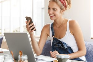 Lovely female checks her bank account on mobile phone application, satisfied to recieve money reward or bonus for good work, involved in distance job, being freelancer, keeps in touch with boss