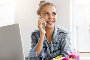 Positive young attractive female talks on digital telephone, calls to friend, being happy to hear good news, works on laptop computer, prepares course paper, enjoys fresh cold cocktail or shake
