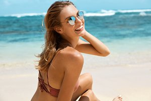 Happy young slim female in eyewear and swimsuit sits on beach against calm sea, enjoys her recreation time and sunny hot weather at coastline. Restful woman poses over beautiful marine landscape