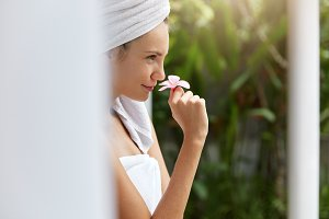 Sideways portrait of lovely female model spends free time at beauty salon in exotic country, wears towel on head and holds small odorous flower, being satisfied after taking spa in outdoor bath