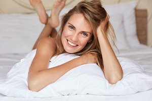 Relaxed female lies in bed on white bedclothes, has good mood in morning, poses at hotel room, has vacations in other country, thinks what do today. Cute woman going to have sleep at bedroom