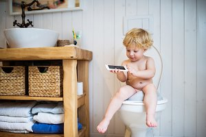 Cute toddler boy with smartphone in the bathroom.