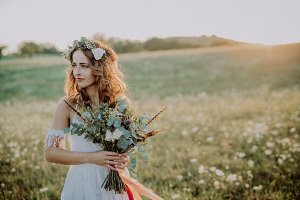 Beautiful young bride at sunset in green nature.