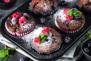 Chocolate orange muffins or cupcakes with berries.