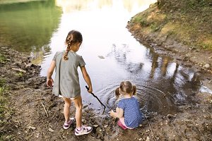 Little girls standing in the lake. Sunny summer.