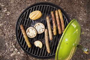 Barbecue grill with sausages, cheese and vegetables.