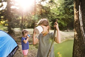 Cute little girls camping outdoors, drinking water.