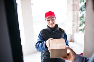A man receiving parcel from delivery woman at the door.