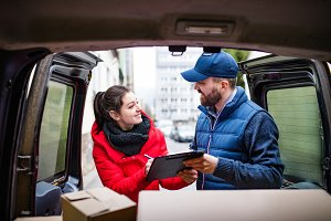 Woman receiving parcel from delivery man.