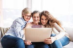 A teenage girl, mother and grandmother with laptop at home.