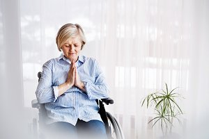A senior woman in wheelchair praying at home.