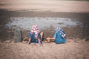 Children sitting on dry ground