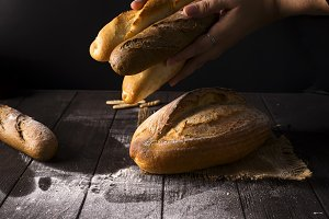 Close-up of woman hands take fresh bread. Dark photo