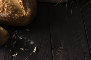 Bakery - gold rustic crusty loaves of bread and buns on black chalkboard background.