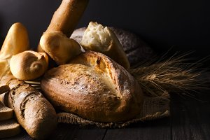 Bakery - gold rustic crusty loaves of bread and buns on black background.