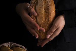 Baker woman holding rustic organic loaf of bread in hands - rural bakery. Natural light, moody still life.