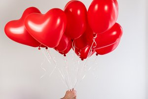 Male hand and red balloons