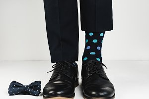 Stylish black shoes, bright socks and a beautiful bow tie on a white background. Style, fashion, beauty