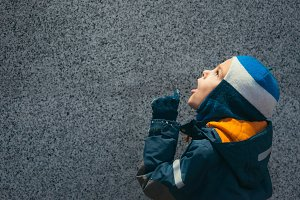 Boy in winter clothes looks up
