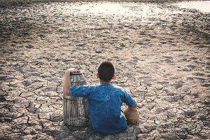 boy sitting on cracked ground