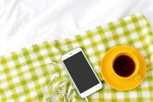 Flat lay phone, yellow cup of tea and flowers on white blanket with green napkin