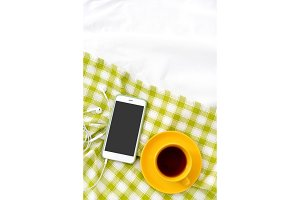 Vertical Flat lay phone, yellow cup of tea and flowers on white blanket with green napkin