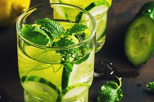 Detox infused water with cucumber and lime. Refreshing clearing drink on a rustic background.