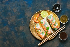 Asian food spring rolls with shrimps on a dark rustic background. Spring rolls in rice paper with a variety of sauces. Top view, space for text.