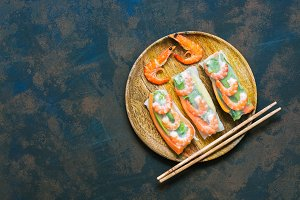 Spring rolls with shrimps in a wooden plate. Vietnamese food. Asian food. Top view, copy space.