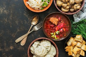 A variety of traditional Russian dishes-borscht,sauerkraut,pickled mushrooms,dumplings. Russian dishes on dark rustic background, top view, copy space.