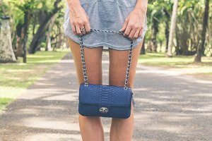 Woman hands with luxury snakeskin handbag outdoors. Tropical fashion exotic concept.