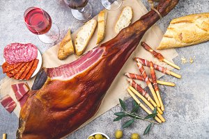 Whole leg HAM JAMON SERRANO and red and rose wine on gray background. Top view. Flat lay