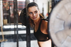 Young sporty woman with barbell