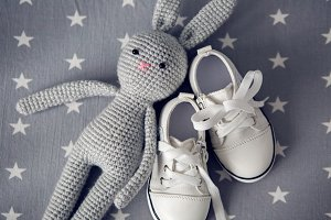 grey knitted toy rabbit, and children's white shoes are on grey background