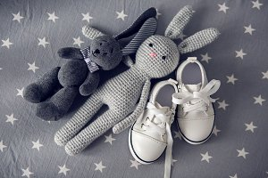two grey knitted toy rabbit and children's white shoes