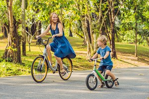 Happy family is riding bikes outdoors and smiling. Mom on a bike and son on a balancebike