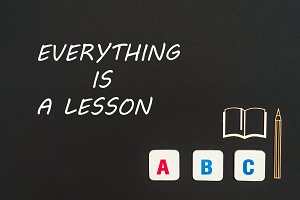 abc letters and chipboard miniature on blackboard with text everything is a lesson