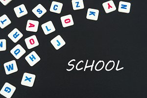 english colored square letters scattered on black background with text school