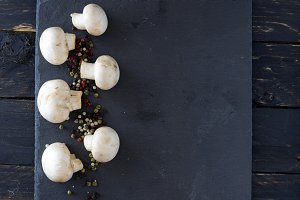 White mushrooms on a slate tray. Natural lighting from the window.