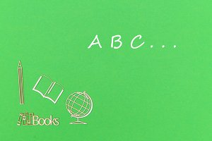 text abc, school supplies wooden miniatures on green background