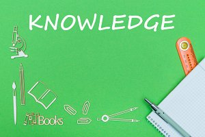 text knowledge, school supplies wooden miniatures, notebook with ruler, pen on green backboard