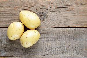Fresh potato on wooden table