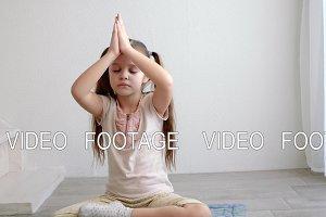 little cute girl sitting in yoga lotus pose and meditates near the window