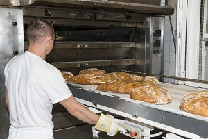A man working with an industrial oven in a bakery