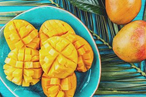 Mango on blue plate. Blue background, palm tree leave, tropical concept