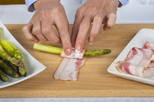 Chef wrapping asparagus with bacon slices