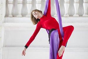 Young woman doing gymnastics on aerial silk