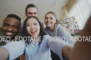 Point of view of asian girl holding smartphone taking selfie photos with cheerful classmates and have fun at university library