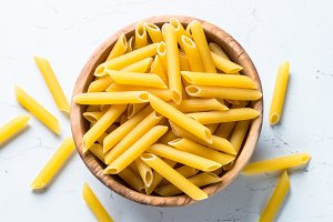 Pasta penne  in wooden bowl on white table.