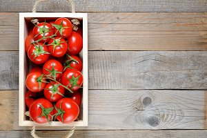 Tomatoes in wooden box on table